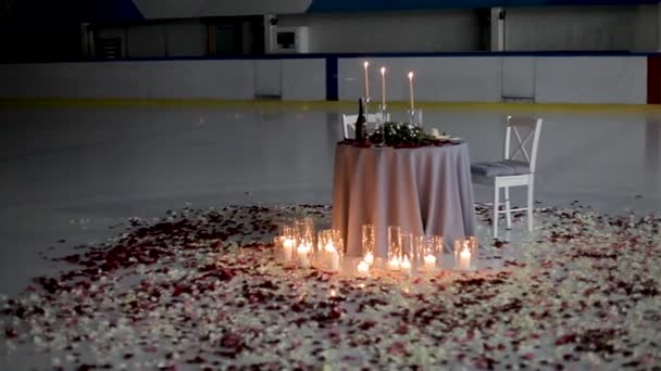 A table for a romantic dinner is decorated with candles and rose petals on ice
