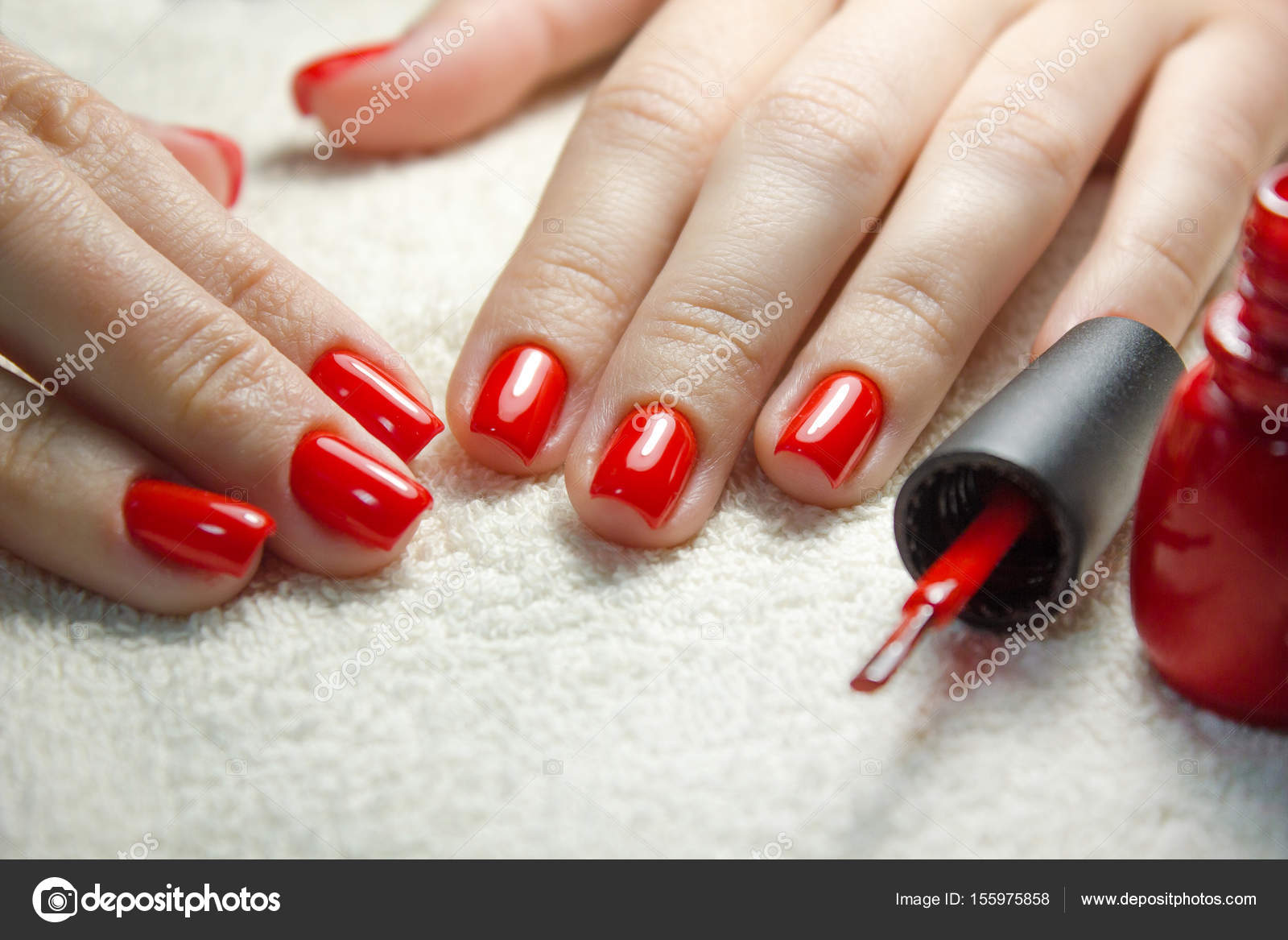 Beautiful manicured womans nails with red nail polish on soft white ...