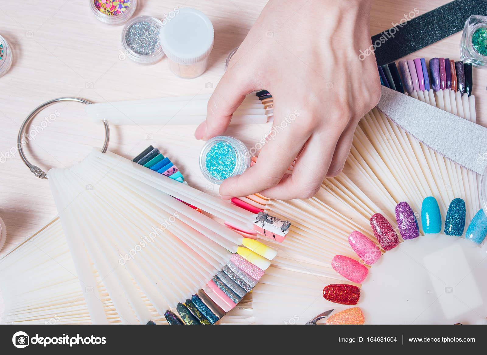 Nagel-Kunst-Konzept. Frau macht Dekoration auf den Nägeln auf weißen ...