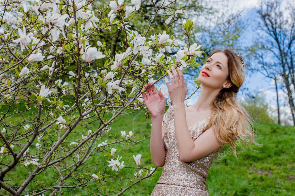 Woman standing close to blooming tree