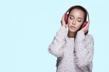 Woman listening to music with red headphones