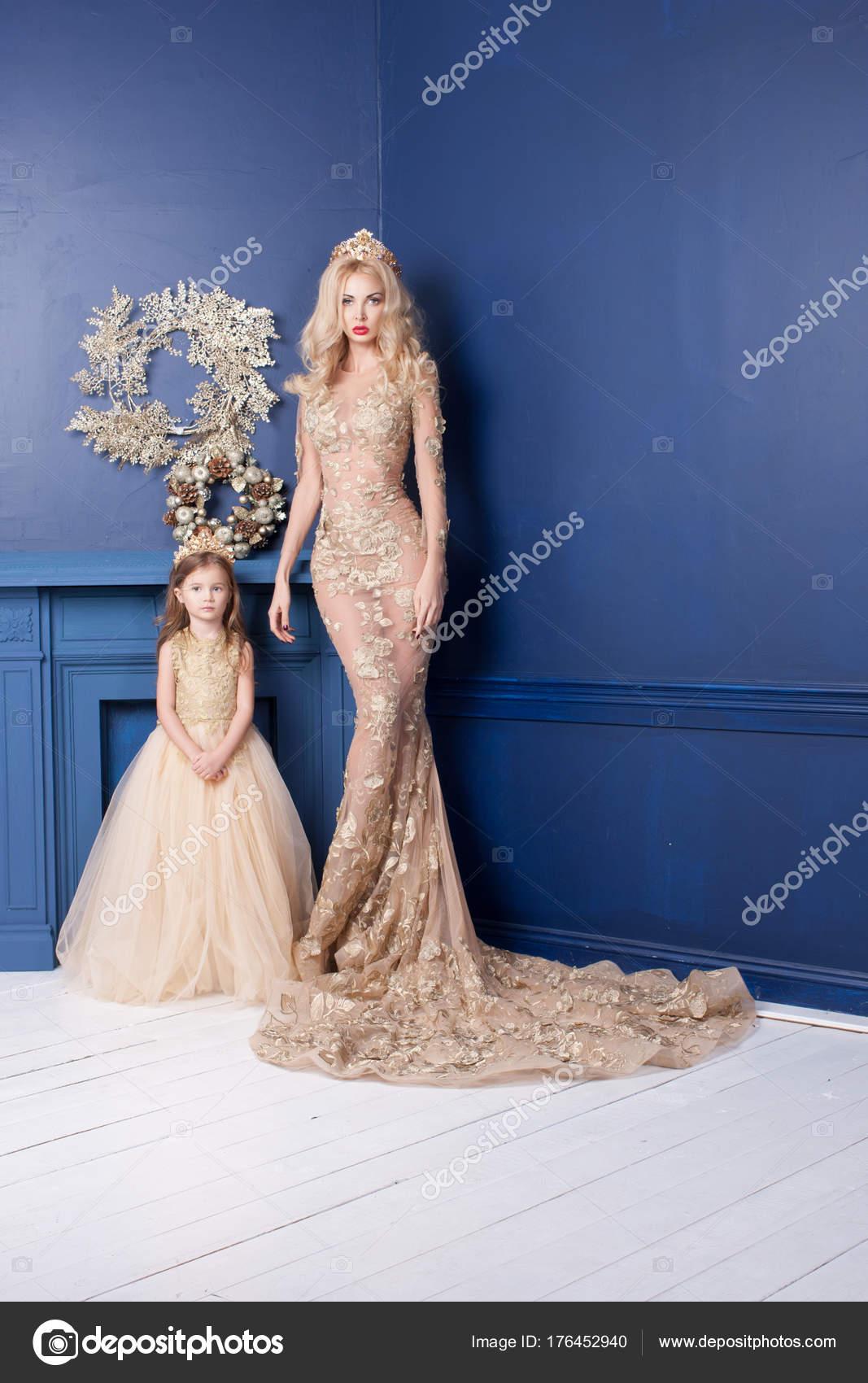 e84c1bcb91b1 Studio shot ομορφιά ξανθιά γυναίκα με χαριτωμένη μικρή κόρη φορώντας  διακοπών χρυσό φορέματα. Ευτυχισμένη οικογένεια στέκεται στο διακοσμημένο  σπίτι ...