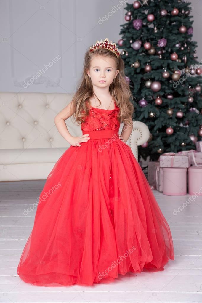 fd715cb7e5bb Χαριτωμένο Μικρό Κορίτσι Που Φοράει Κόκκινο Φόρεμα Στέκεται Κοντά  Στολισμένο — Φωτογραφία Αρχείου © luzgareva  176452332