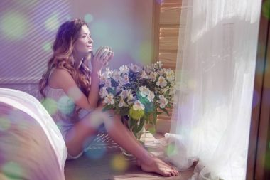 Sun shining into bedroom, beauty woman in white pajamas with coffee cup sitting on floor in bedroom and flowers near window
