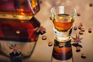 Cognac or liqueur, coffee beans and spices on a glass table.