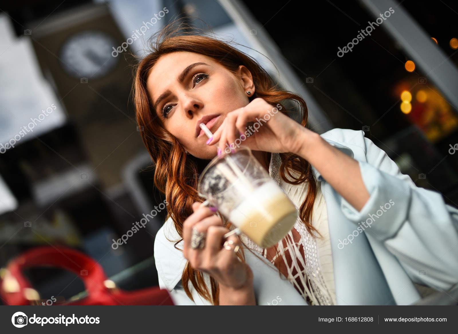0fa042ac0f8f Porträt von einem ziemlich kaukasische Mädchen mit braunen Haaren trinken  Kaffee auf einer Terrasse auf der