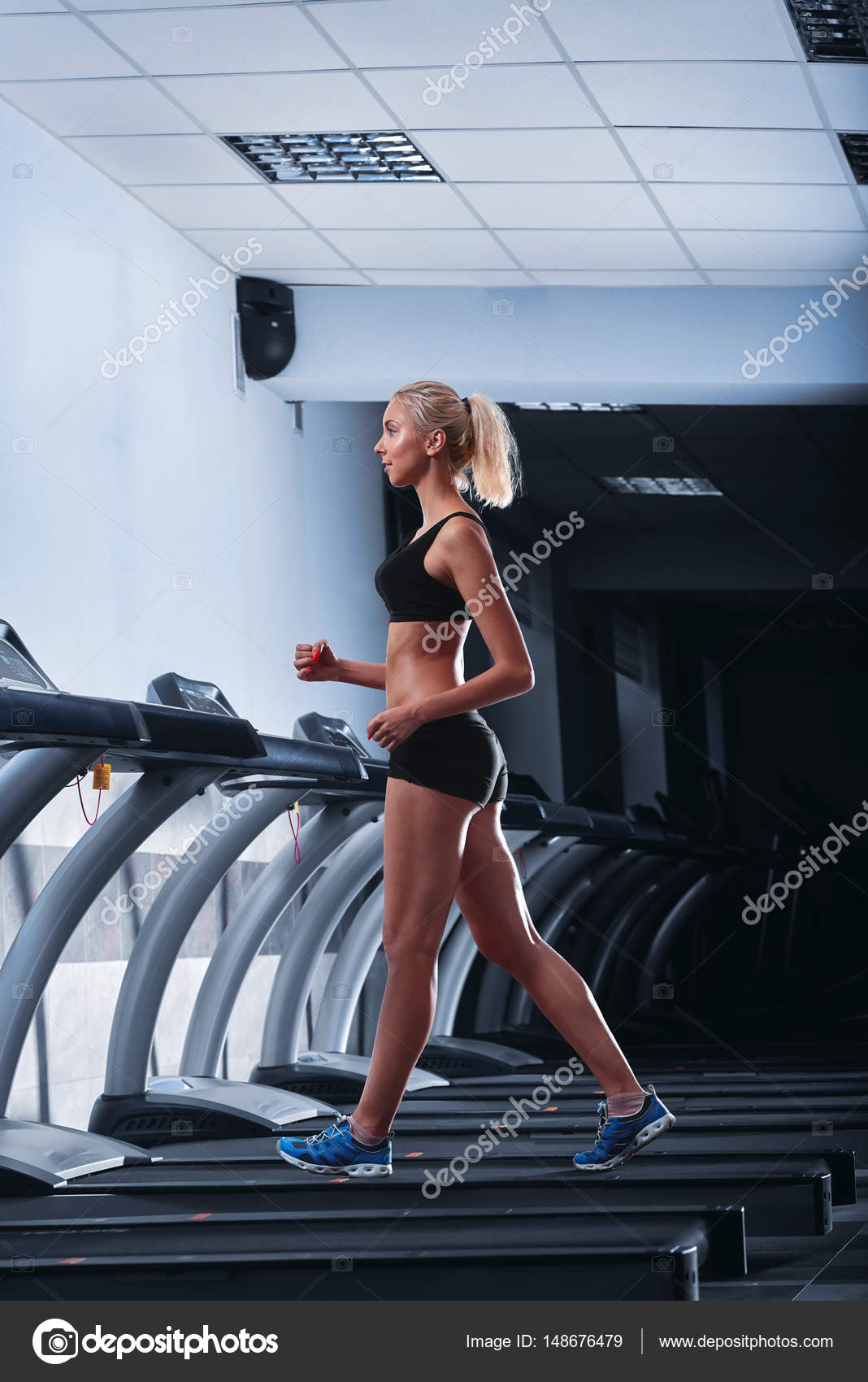 f2d002f043 Young beautiful athletic woman running on a treadmill at the gym — Stock  Photo