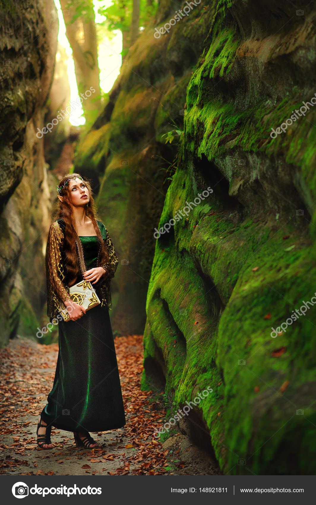 a58a664b3 Longitud vertical la foto de un elfo mujer joven pelo largo hermosa en un vestido  de caminar en el bosque mirando a su alrededor sosteniendo un cosplay de ...