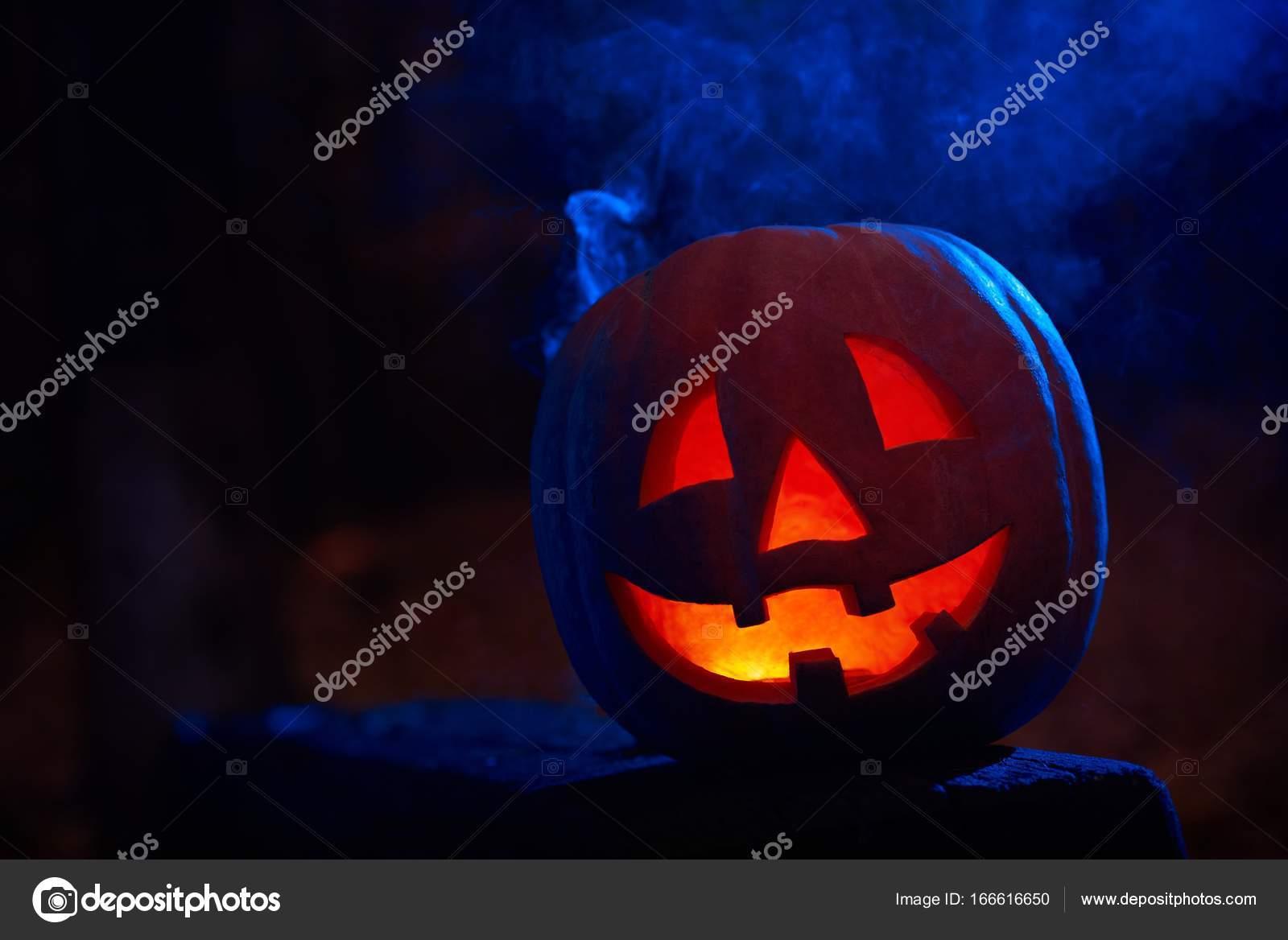 calabaza roja de miedo con el fuego interior y grandes ojos preparados para halloween sentado en la mesa de madera en la sombra