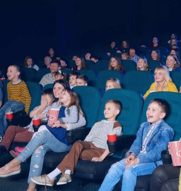 sideview of happy children watching movie.