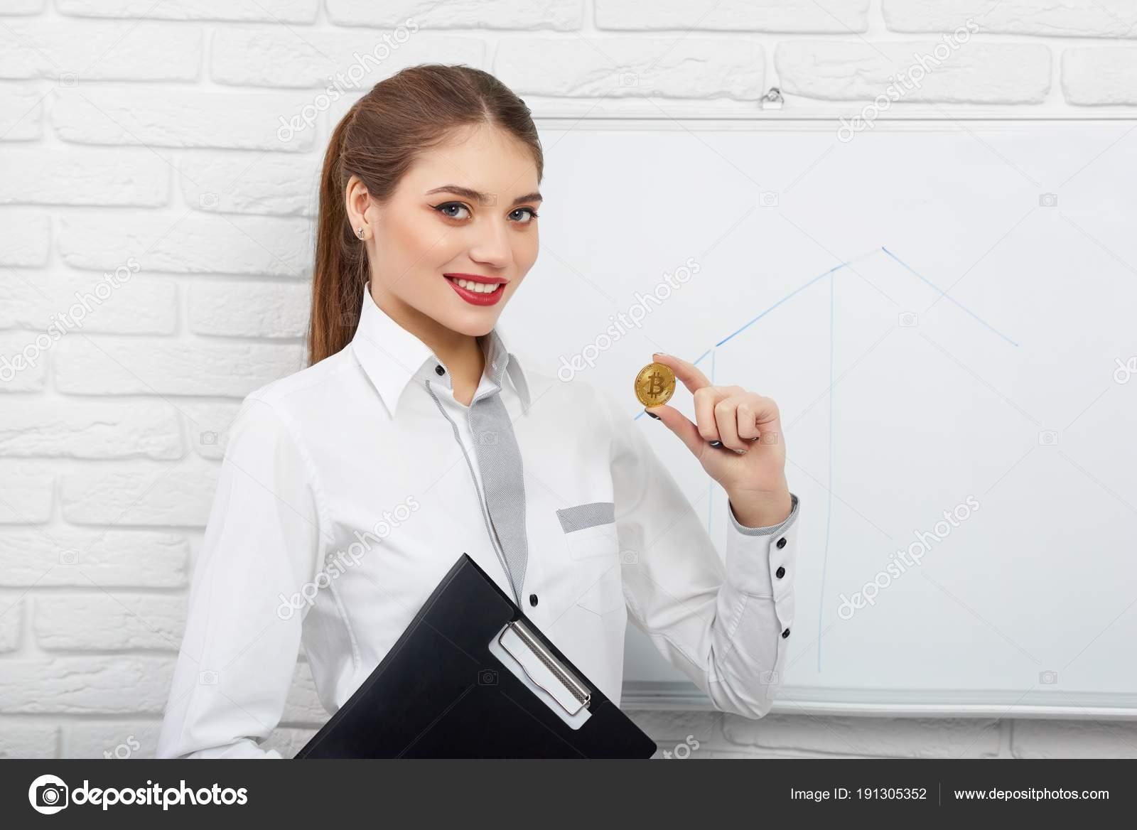696a9331de02 Ελκυστική χαμογελαστή γυναίκα σε λευκή μπλούζα έξυπνη εκμετάλλευση  κρυπτονόμισμα bitcoin και μαύρο φάκελο κοντά Διοικητικό Συμβούλιο λευκό  παρουσίαση ...