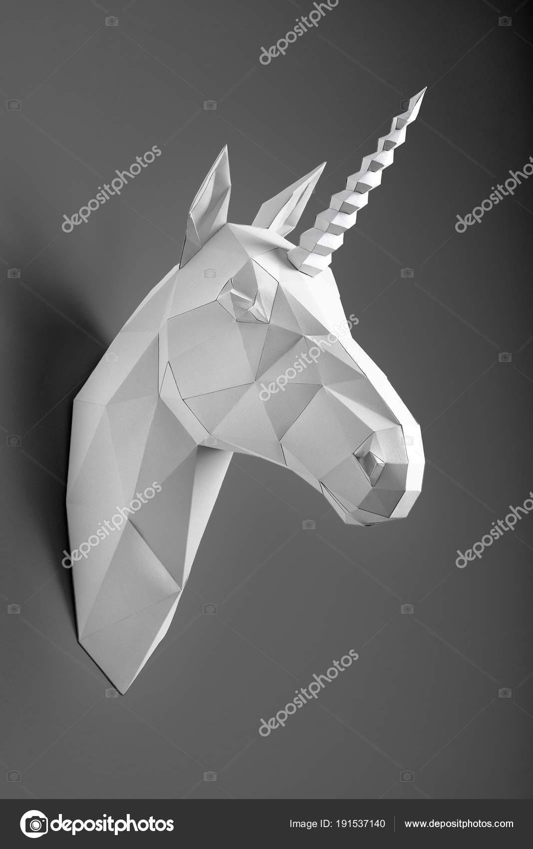 White Paper Unicorns Head Hanging On Dark Graphitic Shadowed Wall Stock Photo