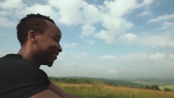 Šťastný africký chlap sedí na vrcholu hory po tréninku