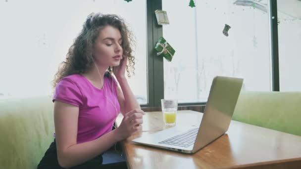 Lächelnde Frau mit Laptop im Café.