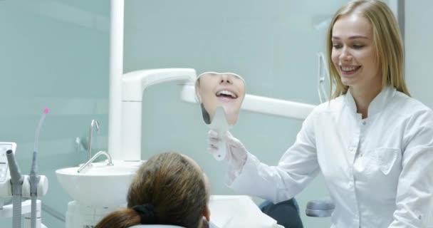 Zubař ukazující pacientův výsledek bělení.