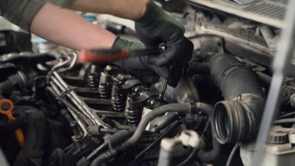 Car mechanic unscrewing spark plugs.
