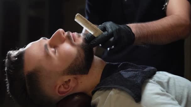 Detailní záběr holiče v černých rukavicích holení klienta s břitvou
