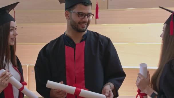 Tři absolventi v županu s certifikáty, mluví.