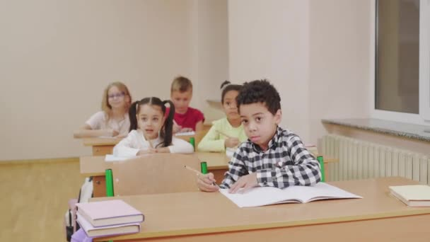 Multiracial children raising hands in classroom.