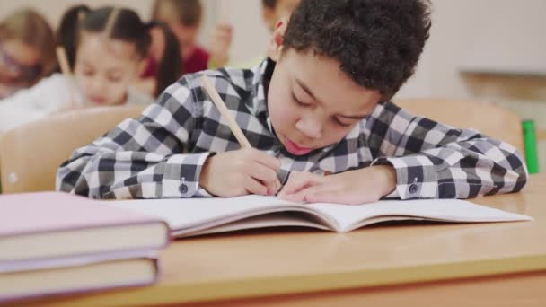 Boy drawing in copybook in classroom.