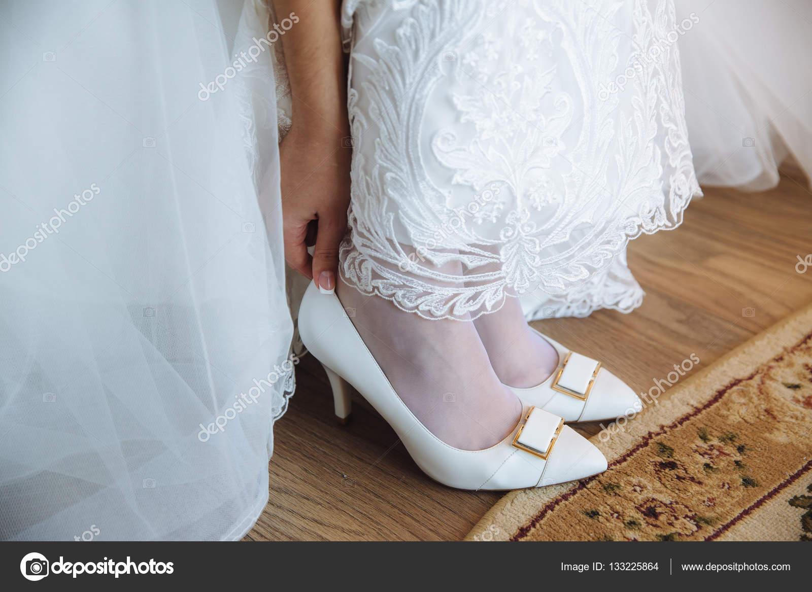 53fd68f4325f Η νύφη φοράει λευκά παπούτσια με τα πόδια στην ημέρα του γάμου — Εικόνα από  ...