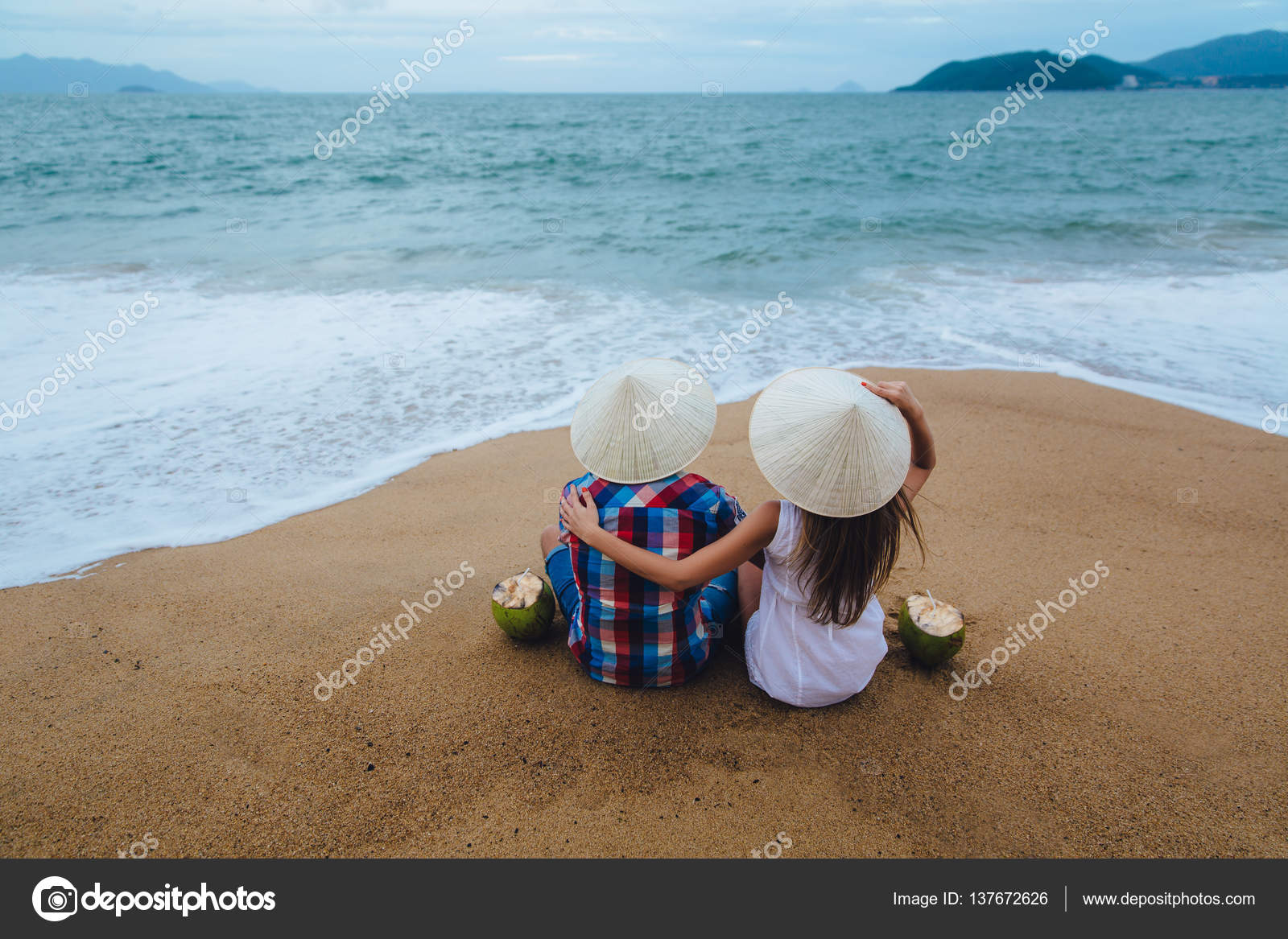 Just Married Couple In Vietnamese Hats Turned Back Sitting On The