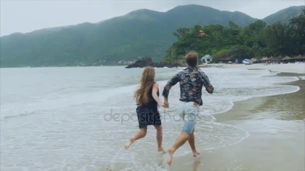 Mladý pár v lásce běžící na pláži u moře, drželi se za ruce, úsměv a smích ve zpomaleném filmu. Koncept šťastnou rodinu a odpočinek