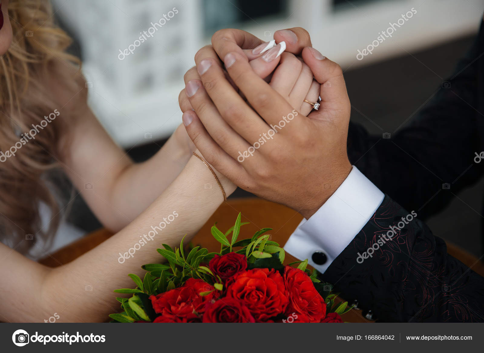 Closeup groom and bride are holding hands at wedding day ang show