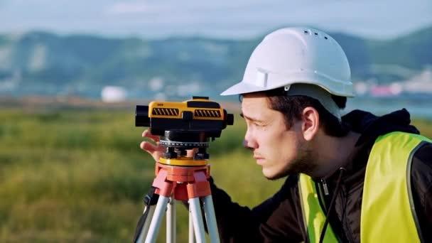 Földmérő mérnök mérésére az építkezésen. Geodéta biztosítja a pontos mérések előtt vállalkozás nagy építkezések. Táj design koncepció