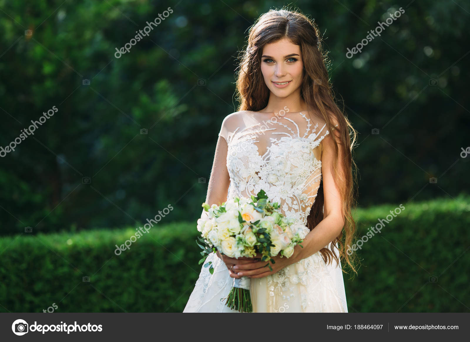 Niedliche junge Braut mit langen Haaren halten ihre Hochzeit Bouquet ...