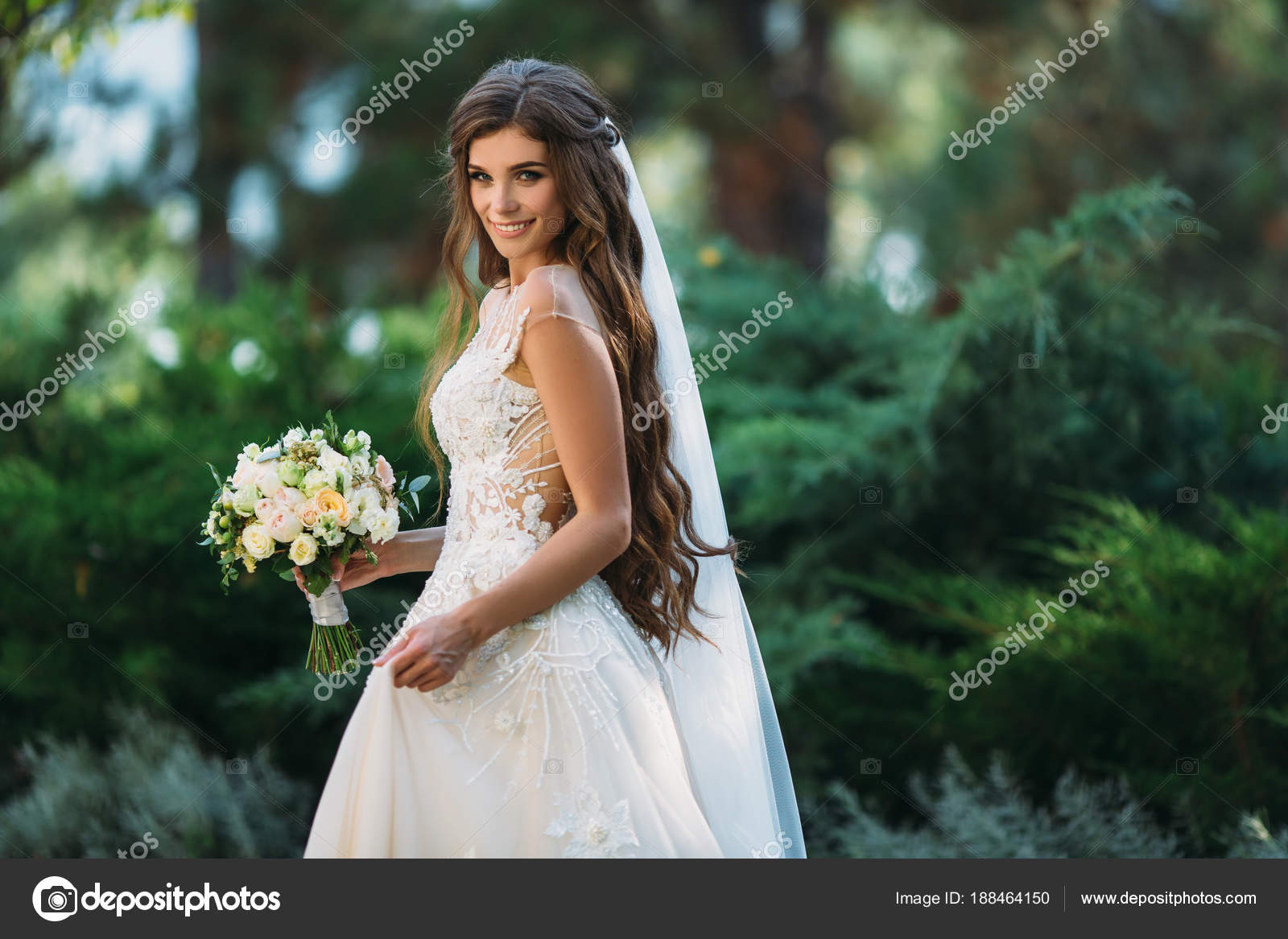 Cute young bride with long hairs holding her wedding bouquet ...