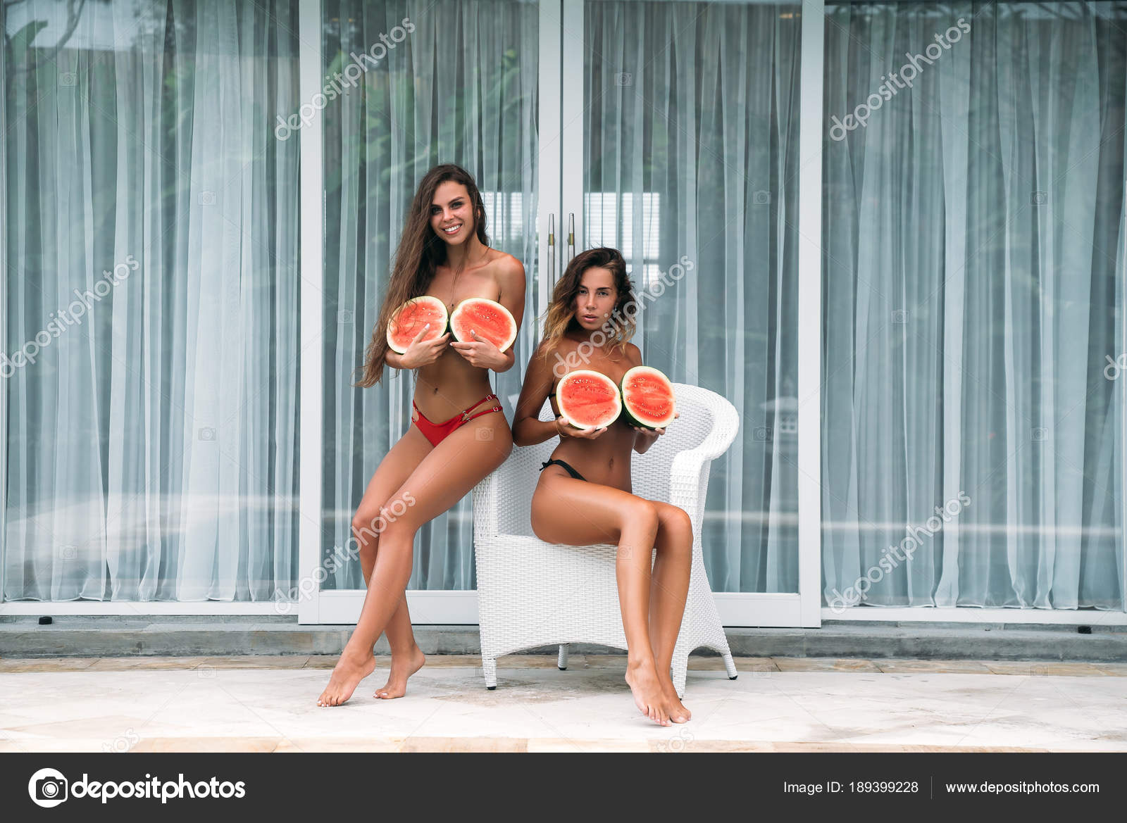 two nice girls with curly hair holds a watermelon in their hands and
