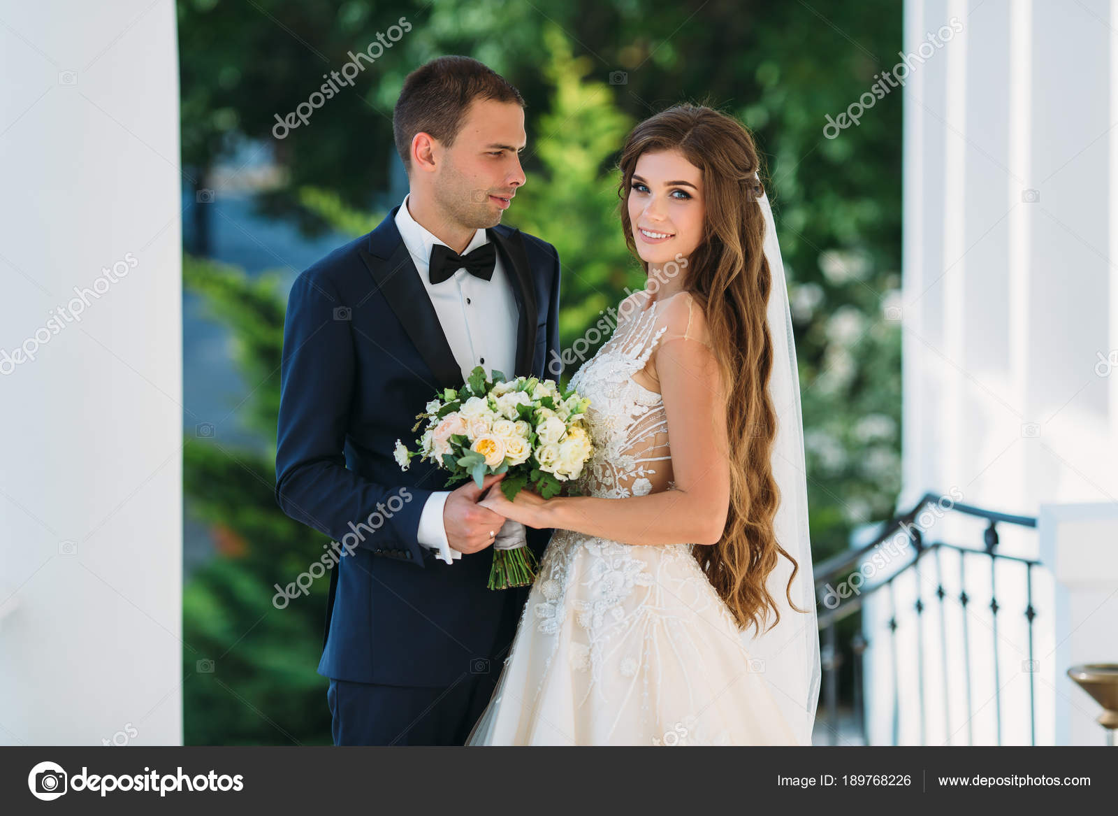 Happy Couple Hugging And Smiling In Garden With Green Trees The