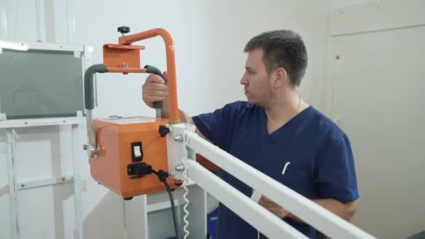 Zblízka muže v lékařské oblečení upraví Rentgenové přístroje. Lékař v nemocnici pracuje s lékařské vybavení
