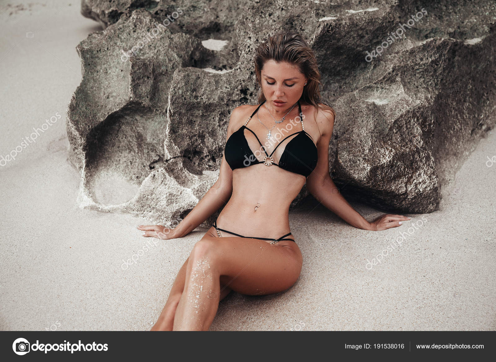 Blond girl with big breasts in a black swimsuit on a white sand beach.  Portrait of a young woman with a beautiful body.
