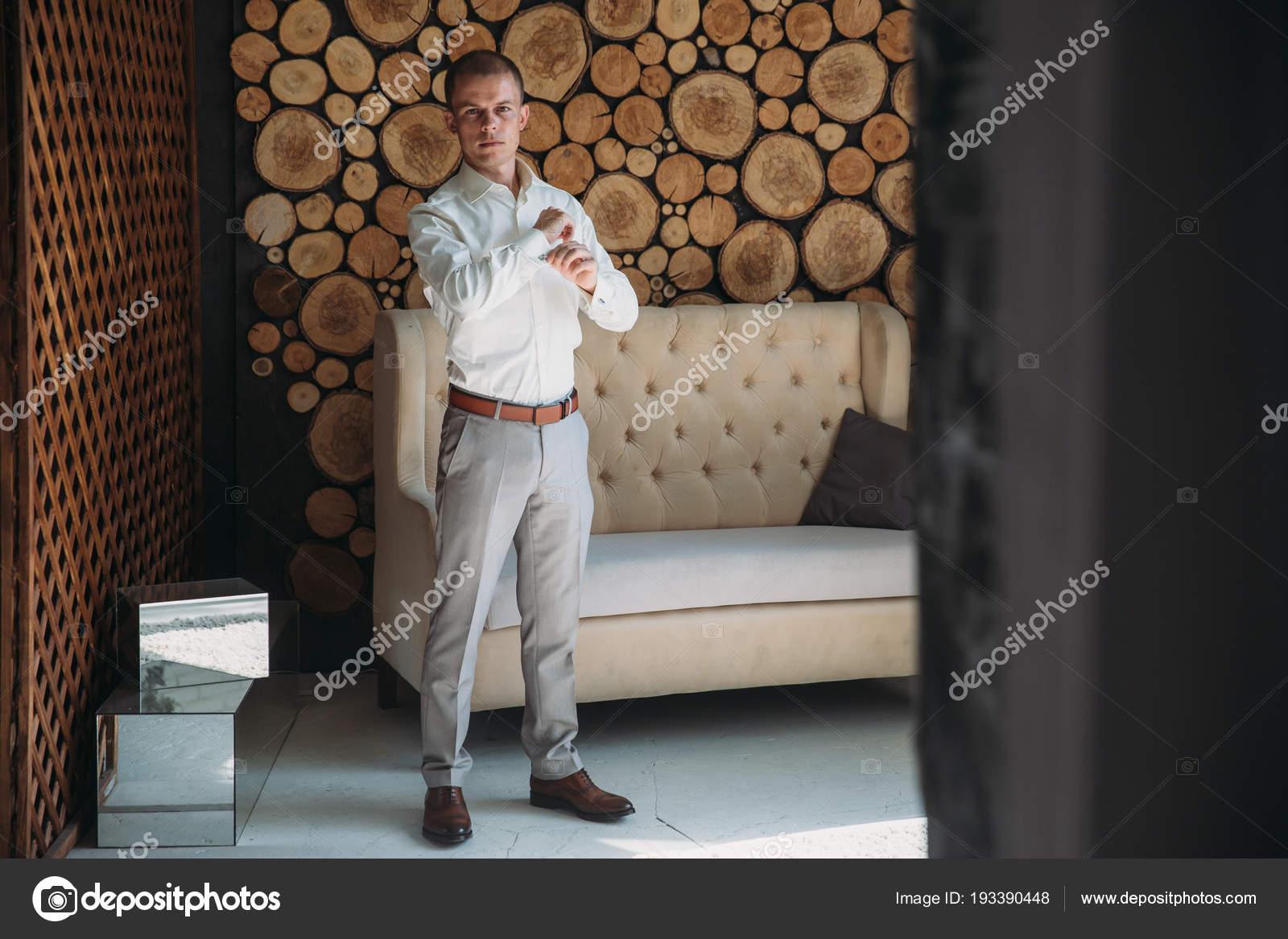 0308081c32cc Προετοιμασία του γαμπρού την ημέρα του γάμου. Ο άνθρωπος φορέματα ένα άσπρο  πουκάμισο και τα μανικετόκουμπα το πρωί στο στούντιο με ένα ξύλινο υπόβαθρο.