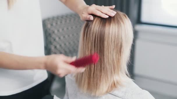 Zblízka ruce kadeřníka hřebeny mokré vlasy ženy před vlasy péče o proceduru