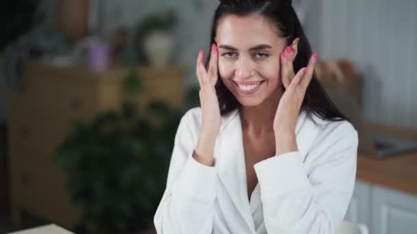 Fiatal nő fürdőköpenyben alkalmazza krém az arcára, és nem arcmasszázs