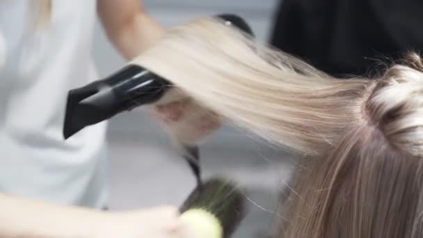 Zblízka, kadeřník vysuší dlouhé blond ženy vlasy s fénem a kulatým hřebenem