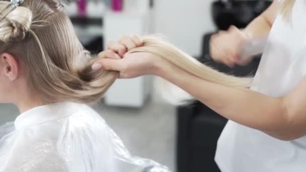 Zblízka, kadeřník česání dlouhé blond vlasy klienta se štětcem