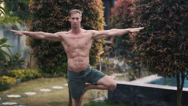Hemdloser Mann mit muskulösem Körper, der Yogaübungen macht, Grün im Hintergrund