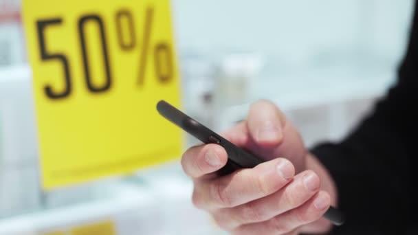Zblízka, mužská ruka drží telefon a posílá zprávu v kosmetickém obchodě