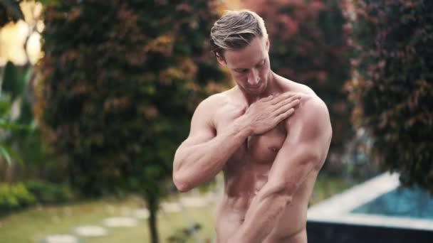 athletische sexy Mann trägt Bräunungsöl auf seinen Körper mit Pool auf dem Hintergrund