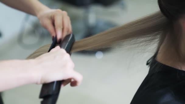 Közelről, fodrász stílus hosszú haj a nő hajvasaló