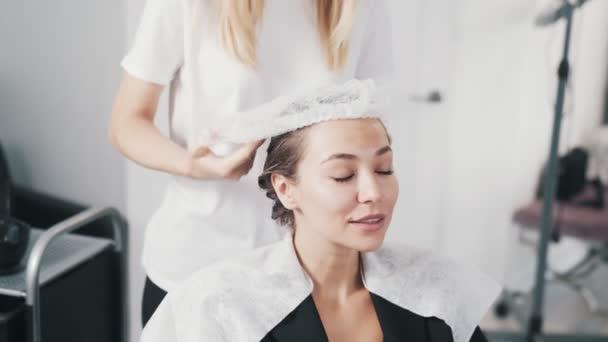 Kadeřník dává jednorázový klobouk na hlavu mladé ženy během péče o vlasy
