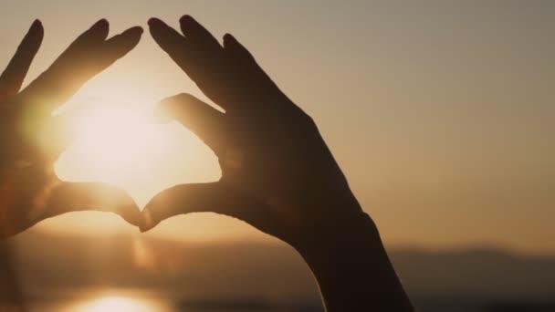 Zavři ruku, ženský ruce dělají srdce a západ slunce na pozadí, pomalý pohyb
