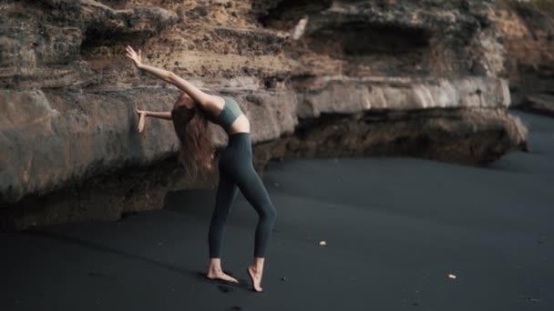 Žena dělá strečink cvičení na černé písečné pláži v blízkosti útesu, zpomalený pohyb