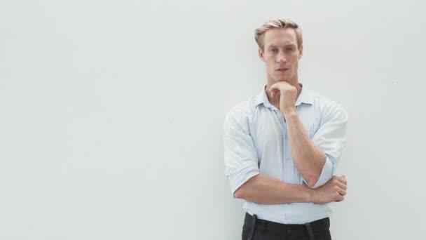 Portrét přemýšlivého blonďáka v košili se zkříženýma rukama na bílém pozadí