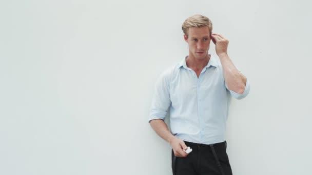 Hezký muž si nasadí bezdrátová sluchátka do uší a poslouchá hudbu