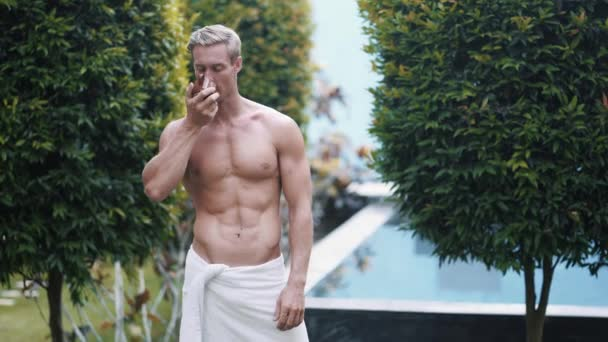 atraktivní muž pije kávu v blízkosti bazénu v zahradě